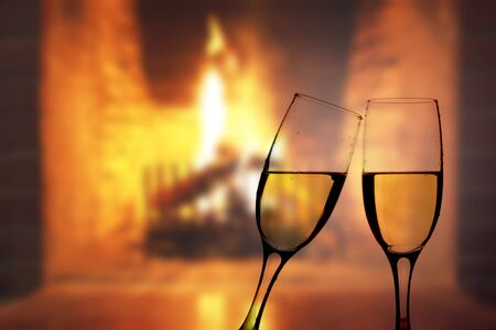 burning fireplace: Two glasses of sparkling champagne in front of burning fireplace Stock Photo