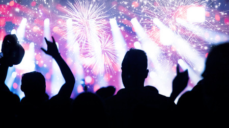 Cheering crowd and fireworks at New Years Eve Stock Photo