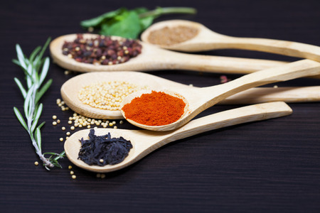 mustard leaf: Various colorful spices on kitchen spoons on black wooden table background - retro styled photo Stock Photo