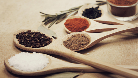 mustard leaf: Various colorful spices on kitchen spoons over grunge wooden table