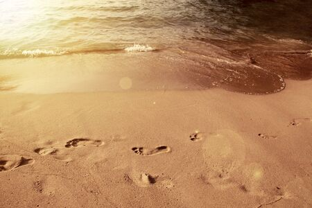 seeker: Beach holiday concept. Footprints on beach. Vintage photo