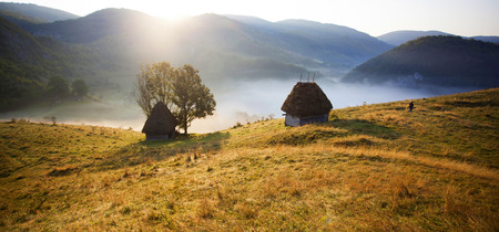 Sunrise in autumn mountains - rural landscape with small cottage in Transylvania, Romania Stock Photo