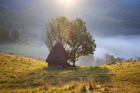 Sunrise in autumn mountains - rural landscape with small cottage in Transylvania, Romania Stock Photo