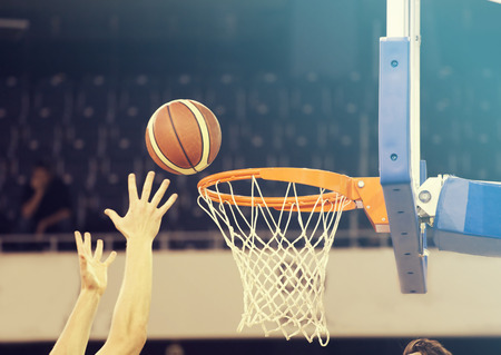 Ball in hoop at basketball game. Basketball players hands Stock Photo