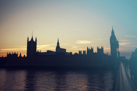 Constitución: Silhouette of Big Ben and Houses of Parliament, London, UK against orange sunset - retro styled photo