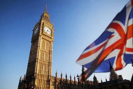 Britse Unie hefboomvlag en Big Ben Clock Tower en het Parlement huis bij stad van Westminster op de achtergrond