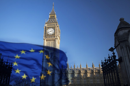 European Union flag and Big Ben Clock Tower and Parliament house at city of Westminster in the background - UK votes to leave the EU, Brexit concept