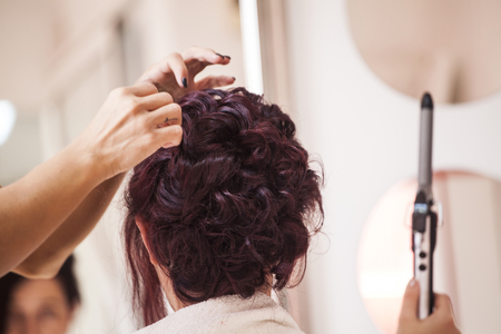 Closeup portrait of bridal morning preparation ceremony. Hair stylist makes the bride a wedding hairstyle