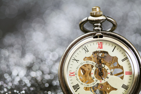 New Years at midnight - Old pocket watch on silver background Stock Photo