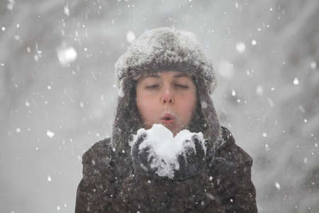 Happy woman blowing snow in winter forest.