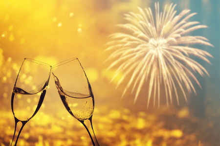 Glasses with champagne against fireworks and holiday lights - Celebrating the New Year Stock Photo