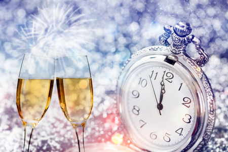 Glasses with champagne against fireworks and clock close to midnight - Celebrating the New Year