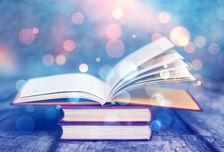 마법의 불빛과 함께 펼쳐진 책. 지혜, 종교, 독서, 상상력, 겨울 휴가의 개념