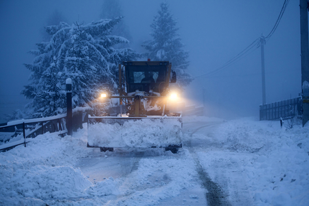 A snow plow clearing a road in winter, early morning