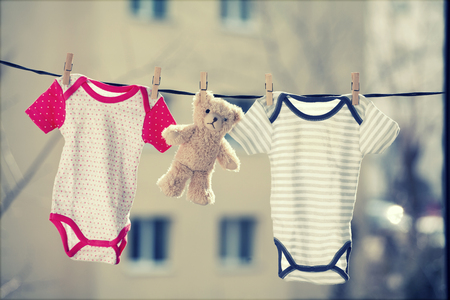 Baby clothes and a teddy bear hanging on the clothesline Stock Photo