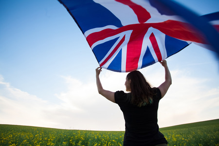 Young woman holding waving Union Jack flag.