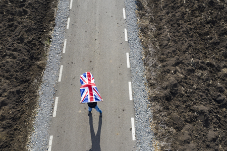 Man holding UK flag on a dirty country road Stock Photo