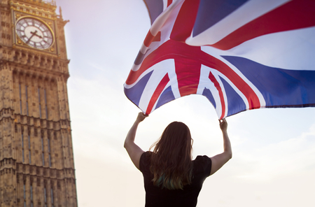 Young woman waving UK flag, Big Ben in the background - brexit concept.