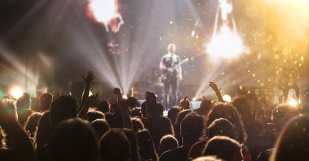 Menigte bij concert - Juichende menigte in heldere kleurrijke podiumverlichting Stockfoto