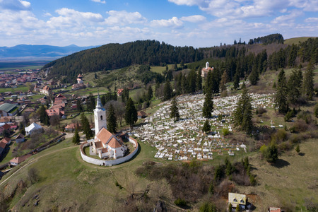 Aerial view of a small village with old church in Transylvania, Romania.