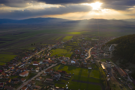 Aerial drone view of beautiful sunset over a small village in Transylvania.