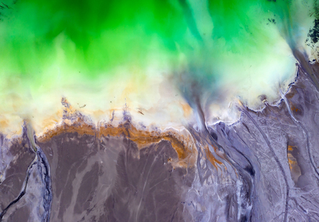 Beautiful aerial pattern of colorful water and mud, shot with a drone located at Geamana, Romania, a formerly village that was covered with toxic waste from a mining operation nearby.