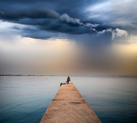 Pier over the lake, stormy sky in the background
