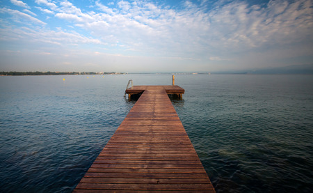 Idyllic view of the wooden pier in the lake with mountain scenery background.