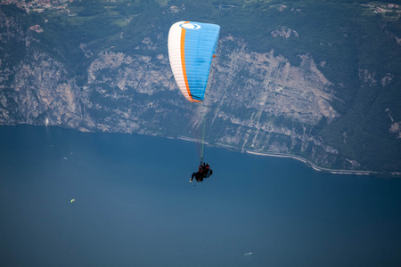 Paraglider flying over mountains and lake in summer day