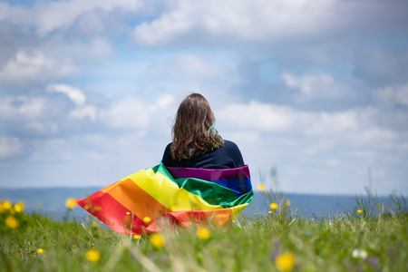 Donna seduta in un prato verde con in mano una bandiera arcobaleno gay. Simbolo bisessuale, gay, lesbica, transessuale. Felicità, libertà e concetto di amore per le stesse coppie