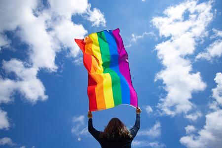 Donna che tiene una bandiera arcobaleno gay sopra il cielo estivo blu. Simbolo bisessuale, gay, lesbica, transessuale. Felicità, libertà e concetto di amore per le stesse coppie Archivio Fotografico