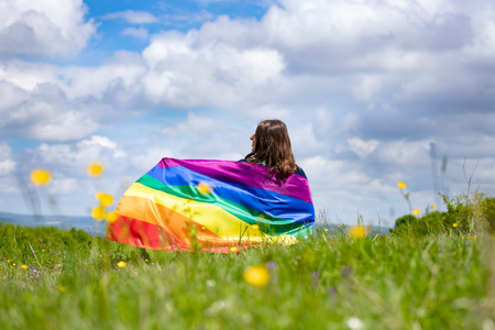 Woman sitting in a green meadow holding a Gay Rainbow Flag. Bisexual,gay, lesbian, transsexual symbol. Happiness, freedom and love concept for same sex couples Stock Photo
