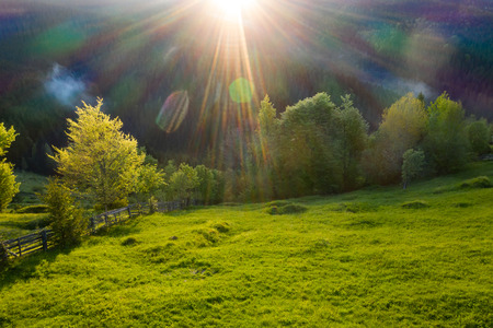 Aerial view of endless lush pastures and farmlands of Transylvania. Beautiful romanian countryside with emerald green fields and meadows. Rural landscape on sunset. Stock Photo