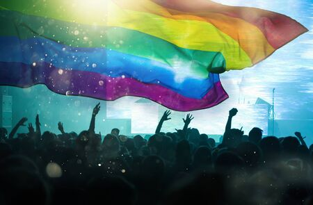 Pride community at a parade with hands raised and the LGBT flag - symbol of love and tolerance Stok Fotoğraf
