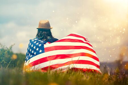 Young woman holding american USA flag. Independence Day or traveling in America concept.