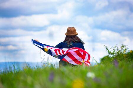 Giovane donna che tiene bandiera americana degli Stati Uniti. Independence Day o viaggiare nel concetto di America.