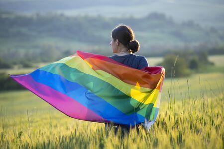 Frau, die eine homosexuelle Regenbogenflagge über blauem Sommerhimmel hält. Standard-Bild