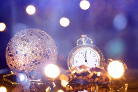 Old golden clock close to midnight and sparkling Christmas decoration - New Year concept Standard-Bild