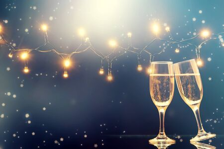 Champagne glasses on sparkling holiday background - Celebrating the New Year Stock Photo