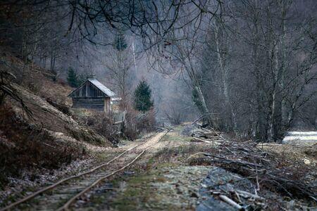 Vieux chalet en bois près des chemins de fer dans les montagnes roumaines. Paysage rural effrayant.