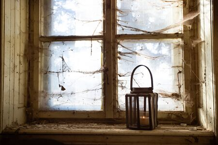 Eerie light of candles in an old window with a cobweb. Concept of horror and Halloween.