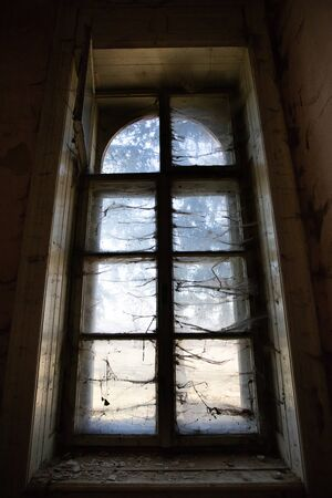 Old abandoned building with spider web near the window. Concept of horror and Halloween.
