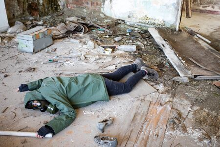 Post apocalyptic survivor in gas mask fallen on the ground in a ruined building. Environmental disaster, armageddon concept. Stock Photo