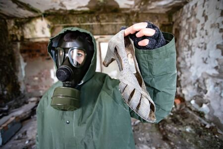 Post apocalyptic survivor in gas mask in a ruined building. Environmental disaster, armageddon concept. Stock Photo