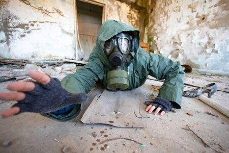 Post apocalyptic survivor in gas mask asking for help in a ruined building. Environmental disaster, armageddon concept. Archivio Fotografico