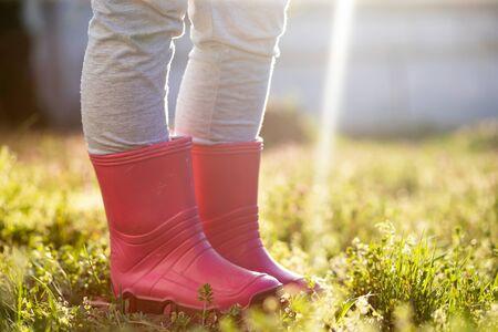 Jambe d'enfant en bottes wellington roses debout dans un jardin de printemps magique.