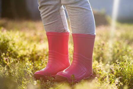 Pierna del niño en botas de agua rosadas de pie en el jardín mágico de la primavera.