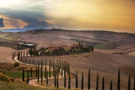 Beautiful Tuscan landscape at sunset after rain with cypress trees. Italy, Europe.