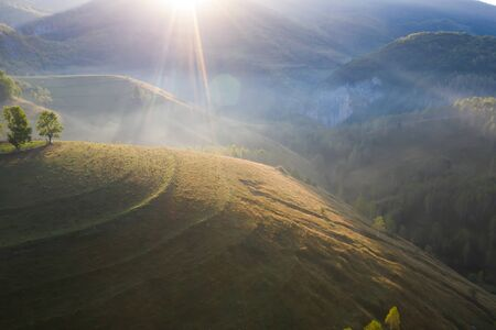 Aerial view of endless lush pastures of Transylvania. Beautiful romanian countryside with emerald green fields and meadows. Rural landscape on sunrise.