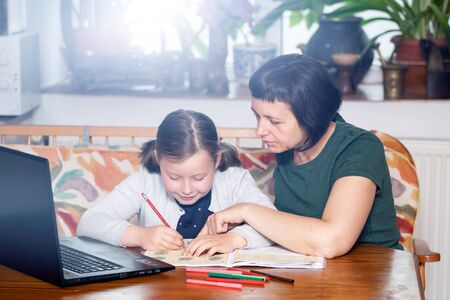 Distance learning-online education. School girl with her mother doing school homework. COVID-19 pandemic forces children online learning.